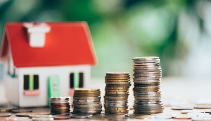 Close-up view of stacked coins and house model, savings concept - Depositphotos_223185564_xl-2015